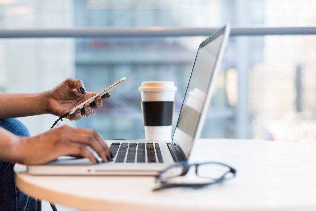 black woman on laptop and smartphone